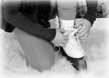Closeup of young figure skater tying skates in black and white Stock Photography
