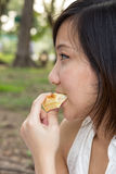 Closeup young girl bite a sandwich in park Stock Images