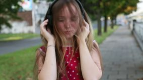 Closeup of a young  girl enjoying music in headphones outdoor. stock video footage