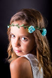 Closeup of a young girl with flower tiara and sober look. Closeup of a young girl with long hair and flower tiara posing with a sober look on a black background Royalty Free Stock Image