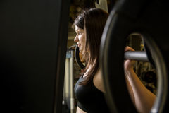 Closeup of a young girl in the gym with a barbell. Stock Images