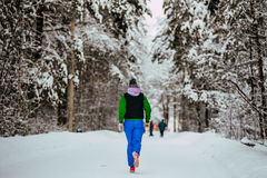 Closeup young girl running snow-covered alley in winter Park Royalty Free Stock Images