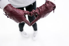 Closeup of young girl shows abstract heart symbol by leather gloves on ice. Concept  love to skates, winter sports. Stock Photos