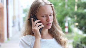 Closeup young girl talking on the phone against a blurred background stock video