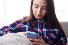 Young girl using telephone while sitting on sofa Royalty Free Stock Photography