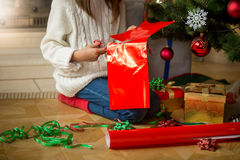 Closeup of young girl wrapping presents under Christmas tree. Closeup image of young girl wrapping presents under Christmas tree Royalty Free Stock Photo