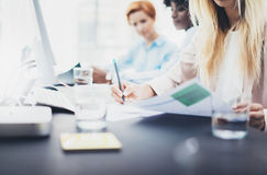 Closeup of young girls coworkers discussing together business project. Beautiful blonde woman signing documnet on workplace in off Royalty Free Stock Images