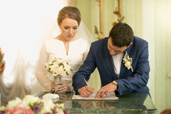 Closeup of young groom signing wedding contract at registry offi Royalty Free Stock Image