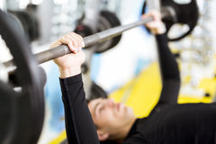 Closeup of young handsome man doing exercises on a bench press Royalty Free Stock Images