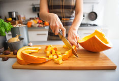 Closeup on young housewife cutting pumpkin Royalty Free Stock Photography