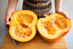 Closeup on young housewife cutting pumpkin Royalty Free Stock Images