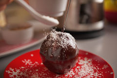 Closeup on young housewife decorating apple in chocolate glaze Stock Images