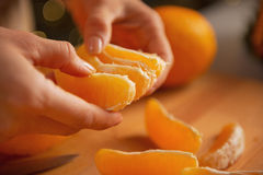 Closeup on young housewife dividing orange slices Stock Photos