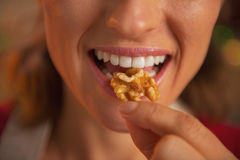 Closeup on young housewife eating walnuts Stock Photos