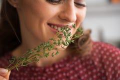 Closeup on young housewife enjoying fresh thymus Stock Photos