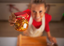 Closeup on young housewife jar with honey nuts Royalty Free Stock Images