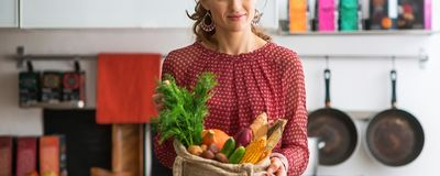 Closeup on young housewife with local market purchases in kitch Royalty Free Stock Image