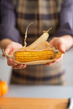 Closeup on young housewife showing corn Royalty Free Stock Images