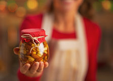 Closeup on young housewife showing jar with honey nuts Royalty Free Stock Images