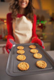Closeup on young housewife showing pan of fresh cookies Royalty Free Stock Photo