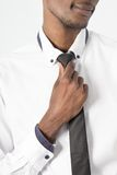 Closeup of young man adjusting his tie Stock Images