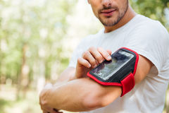 Closeup of young man athlete using mobile phone in handband. Outdoors in the morning Stock Photos