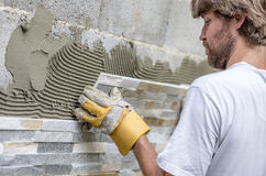 Closeup of young man with a beard precisely placing an ornamental tile on a wall. Covered with glue royalty free stock photos