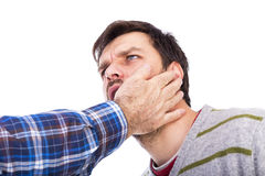 Closeup of young man being slapped in the face. Over white background Stock Image
