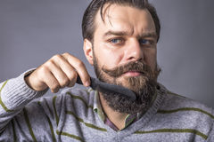 Closeup of young man brushing his beard Royalty Free Stock Photography