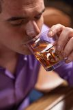 Closeup of young man drinking alcohol drinks. Stock Photo