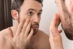 Closeup of young man examining his eye in mirror. Royalty Free Stock Image