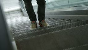 Closeup young man feet in white snickers on escalator stock footage