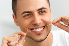 Closeup of young man flossing his teeth. Cleaning teeth with den Royalty Free Stock Images