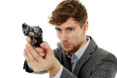 Closeup of a young man with a gun. Handsome young man aiming the gun to an invisible target, with selective focus Stock Photography