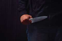 Closeup of a young man hand, holding a knife, about to attack, o Stock Photography