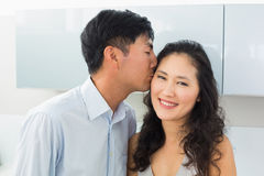 Closeup of a young man kissing woman in kitchen Stock Photography