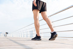 Closeup of young man legs walking on wooden terrace. Closeup of young man legs in black shorts and sneakers walking on wooden terrace Royalty Free Stock Photography