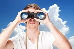 Closeup of young man looking through binoculars Stock Photo
