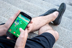 Closeup of a young man playing Pokemon Go Stock Photo