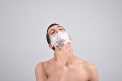 Closeup of young man preparing to shave, he puts foam on his c Royalty Free Stock Images