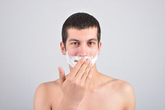 Closeup of young man preparing to shave, he puts foam on his c Stock Photo