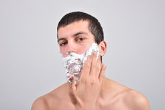 Closeup of young man preparing to shave, he puts foam on his c Royalty Free Stock Image