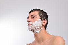 Closeup of a young man preparing to shave, he puts foam on his c Stock Photo