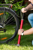 Closeup of young man pumping bicycle tyre Royalty Free Stock Photo