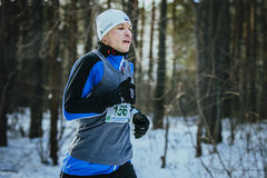 Closeup of young man running in winter woods Stock Images