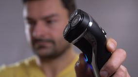A closeup of a young man shaving his beard off with an electric shaver. A closeup of a young man shaving his beard off with an electric shaver stock video footage