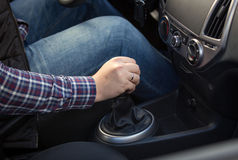 Closeup of young man shifting manual gearbox in car Royalty Free Stock Image