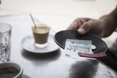 Young man paying the bill in the terrace of a cafe. Closeup of a young man sitting at a table in the terrace of a cafe paying the bill with a five euros banknote Stock Image