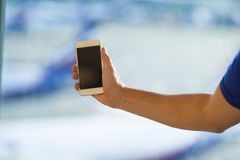Closeup of young man use smart phone in airport Stock Photo