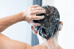 Closeup young man washing hair with with shampoo in the bathroom, health care concept, selective focus royalty free stock images